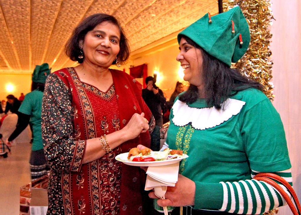 . Enjoying good food and talk at Enterprise Bank\'s holiday celebration are Enterprise Bank employee\'s  L-R, Jasmine Pandit of NH, and Kruti Shah of Westford. SUN/ David H. Brow