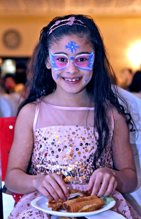 . Here sporting a Winter Fariy face is Jelexa Cortes 9 of Lowell, as she takes in some food and in a front row seat at the Enterprise Bank\'s 3nd Annual International  Holiday Celebration in Lowell. SUN/ David H. Brow