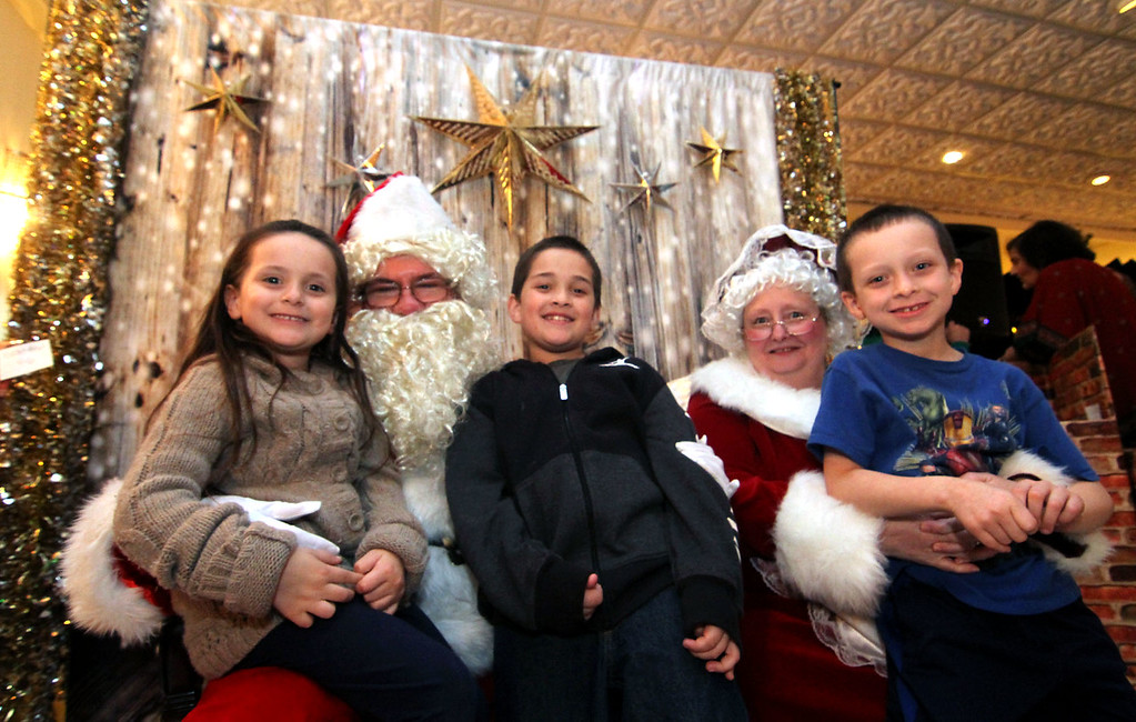 . Here these kids give Mr & Mrs Santa Claus, (played by John Moynihan and Faith Walsh, both Enterprise Bank employee\'s), ideas for gifts are kids L-R, Payton Moro, 5, Darrian Moro,8, and William Moro,7 and from Methuen. SUN/ David H. Brow