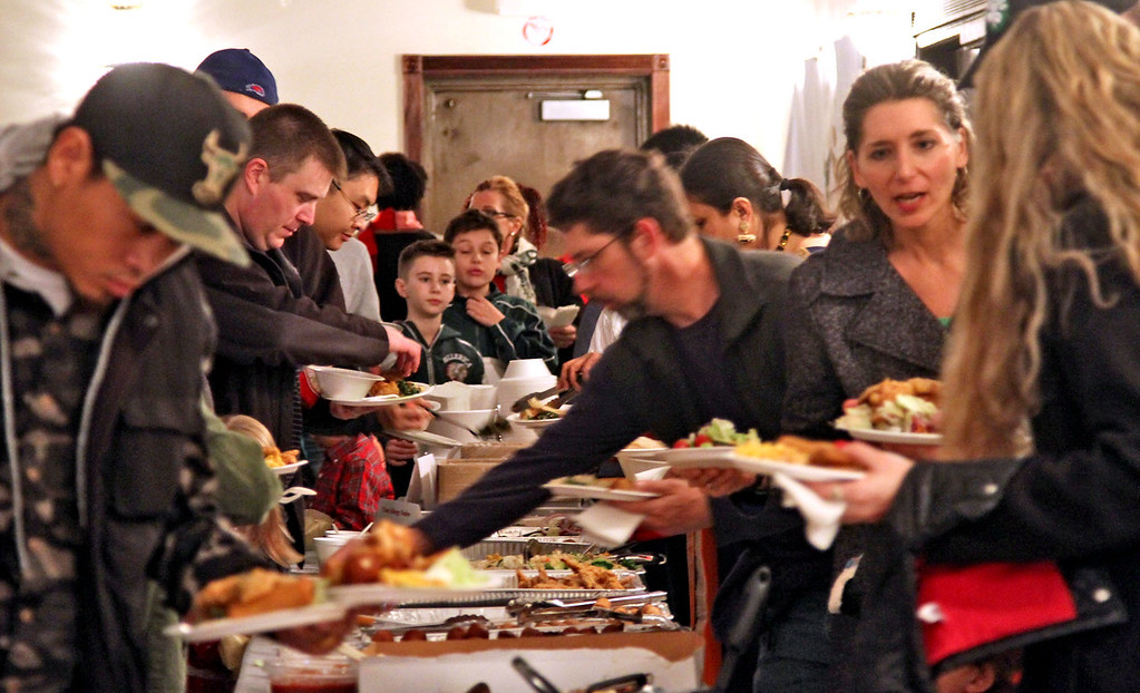 . Folks at the food line at the Enterprise Bank\'s 3nd Annual International Holiday Celebration in Lowell. SUN/ David H. Brow