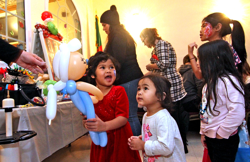 . All smiles is Caroline Voeun,4, of Lowell, after receiving a doll balloon from balloon artist Robin Sullivan, Caroline\'s other family members next to her L-R, Paige Voeun,2, Presley Voeun,4, and Olivia Voeun,9, all at the Enterprise Bank\'s holiday celebration. SUN/ David H. Brow