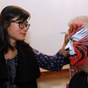 Putting final touches of a painted tiger face on Jack Clancy (CEO of Enterprise Bank), is Annie Trombly of Fun Face Express, at the 3nd Annual Enterprise Bank's Holiday celebration. SUN/ David H. Brow