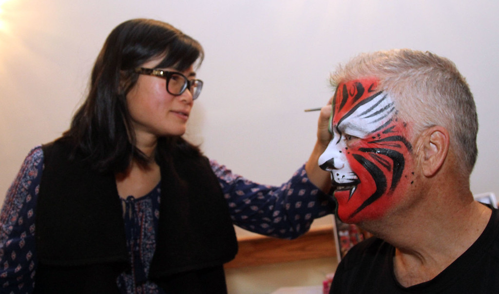 . Putting final touches of a painted tiger face on Jack Clancy (CEO of Enterprise Bank), is Annie Trombly of Fun Face Express, at the 3nd Annual Enterprise Bank\'s Holiday celebration. SUN/ David H. Brow