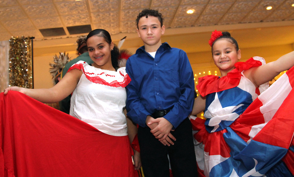 . Shown here after preforming Hispanic Dance at Enterprise Bank\'s holiday celebration is L-R, Nayelitza Bermudez, 16, Jose Molina, 14 and Luz Molina, 10, they are from the Center for Bilingual Services:Acre Girls, and from Lowell. SUN/ David H. Brow