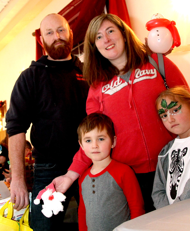 . Taking in the crafts at the Lowell Sun Santa raffle table are L-R, Phil Bicknell his wife Tara Bicknell and children Brayden, 5 and Ryleigh, 7, all from Chelmsford, and at the Enterprise Bank\'s holiday celebration. SUN/ David H. Brow