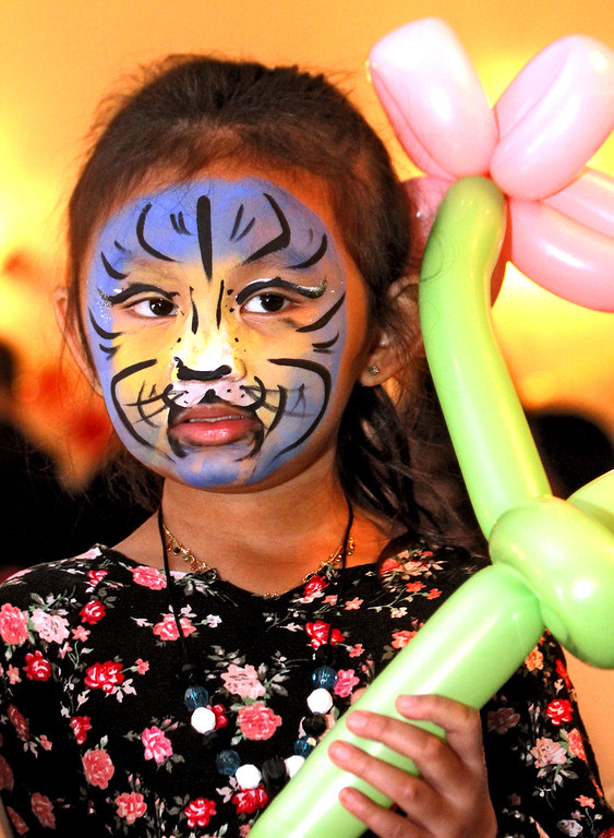 . Taking in the sights and sounds of the Enterprise Bank\'s 3nd Annual International Holiday Celebration is Lilly Ky, 5, of Lowell, with her  Tiger Face and Balloon art. SUN/ David H. Brow