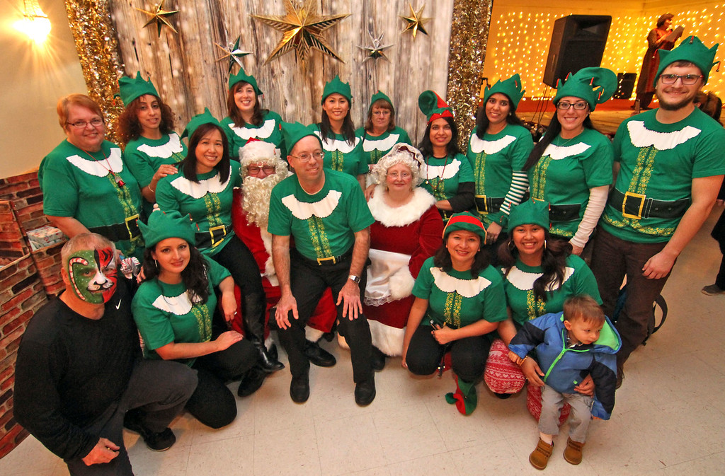 . Enterprise Bank elfs with Mr & Mrs Santa Claus at the bank\'s 3nd Annual International Holiday Celebration in Lowell. SUN/ David H. Brow