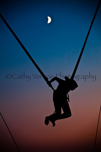 A vertical bungy jumper as the moon rises from the pink glow of the sunset. Taken from Brighton Beach, UK