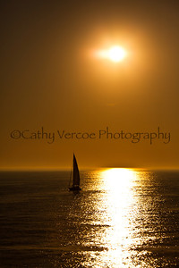 A yacht motors across the bay through the path of the setting sun. Taken from Brighton Pier, UK