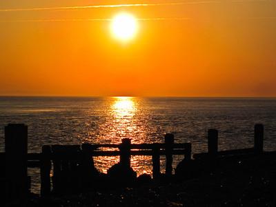 The sun sets over an old coastal fence at Hurst Castle, UK.