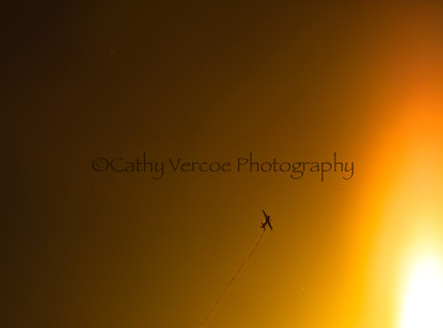 A plane flies across the edge of the setting sun. Taken from Brighton Pier, UK