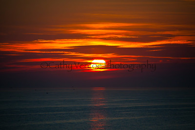 The sun goes down through the clouds on the horizon. Taken from Brighton Pier, UK