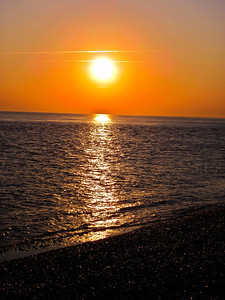 The sun sets over the shingle beach that leads to Hurst castle, UK.