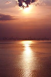 The sun descends through the clouds toward the horizon. Taken from Needles Park, IOW, UK