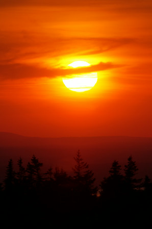 A setting sun over Maine's Cadillac Mountain paints a eerie red hue over the landscape.