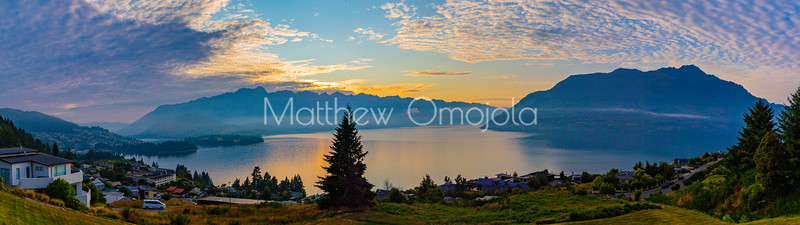 Panorama Sunrise over the Southern Alps, Kā Tiritiri o te Moana, on lake Wakatipu, Queenstown New Zealand. Low clouds and golden sun reflections over lake Wakatipu.