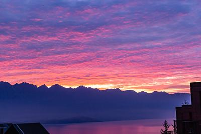 Sunrise over the Southern Alps, Kā Tiritiri o te Moana, and lake wakatipu, Queenstown New Zealand. Pink, purplish and golden reflections on the lake.