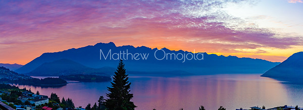 Watching sunrise from my hotel restaurant verandah in Queenstown. Panorama sunrise over the Southern Alps, Kā Tiritiri o te Moana, on lake Wakatipu, Queenstown New Zealand. Beautiful sky colors and low clouds over lake Wakatipu. Sky reflections on the lake.