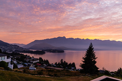Sunrise over the Southern Alps, Kā Tiritiri o te Moana, and lake wakatipu, Queenstown New Zealand. Sky and mountain reflections in the lake.