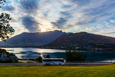 Sunrise over the Southern Alps  Kā Tiritiri o te Moana on lake Wakatipu, Queenstown New Zealand.  Reflections in the lake of sun rays, clouds and mountains