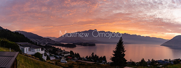 Panorama of Sunrise over the Southern Alps, Kā Tiritiri o te Moana, and lake wakatipu, Queenstown New Zealand.