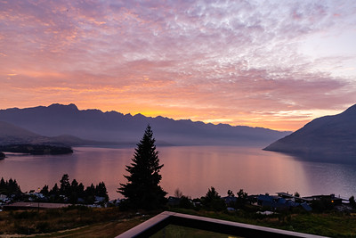 Sunrise over the Southern Alps, Kā Tiritiri o te Moana, and lake wakatipu, Queenstown New Zealand. Reflections in the lake.