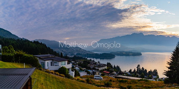 Panorama sunrise over the Southern Alps,  Kā Tiritiri o te Moana, on lake Wakatipu, Queenstown New Zealand. Low clouds over lake Wakatipu. Hillside homes of Queenstown.