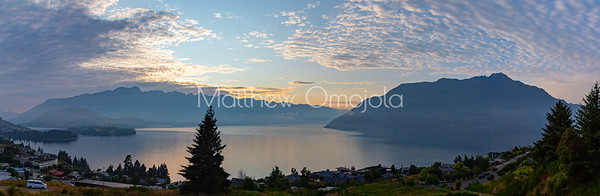 Panorama Sunrise over the Southern Alps,  Kā Tiritiri o te Moana, on lake Wakatipu, Queenstown New Zealand. Low clouds over lake Wakatipu.