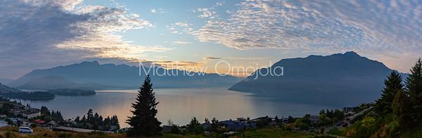 Panorama Sunrise over the Southern Alps,  Kā Tiritiri o te Moana, on lake Wakatipu, Queenstown New Zealand. Low clouds over lake Wakatipu.