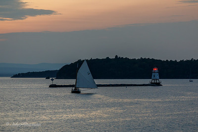 Sailboat at Burlington Breakwater North Light in Sunset Afterglow