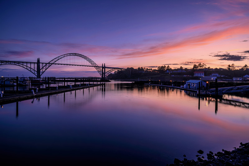 Sunset over the Yaquina Bay Bridge that links Newport, Oregon with South Beach has been called The Green Lady for the green arch that rises 600 feet into the sky.