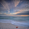 Long exposure of waves, clouds and seaweed at sunset on Bowman Beach, Sanibel Island, Florida