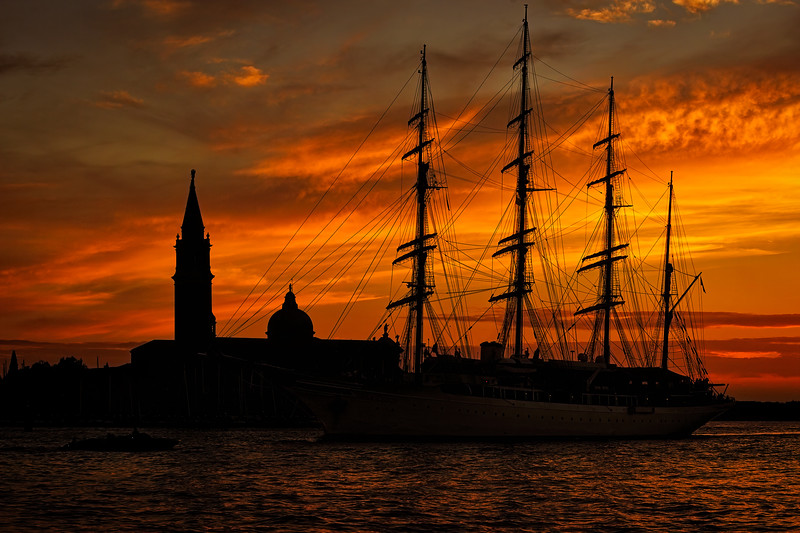 Silhouette of tall ship at sunset with view of Church of San Giorgio Maggiore on the island of San Giorgio Maggiore from St. Mark's Square, Venice, Italy