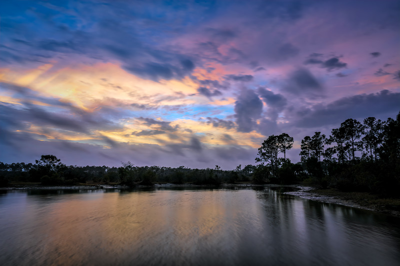 Clouds from the approaching rainstorm at sunrise over pond at Babcock Wildlife Management Area near Punta Gorda, Florida