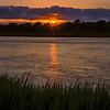 The sun sets behind trees along the Platte River near the Gibbon Bridge, Gibbon, Nebraska