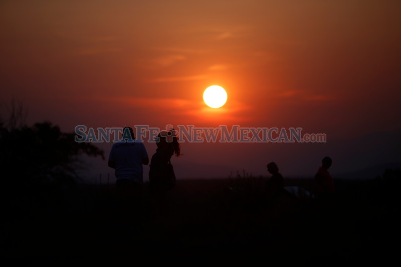 Ben Rettke of Los Alamos and Laura Acquaviva of Santa Fe watch the sunset together from the Cross of the Martyrs on Monday August 20, 2018. Luis Sánchez Saturno/The New Mexican