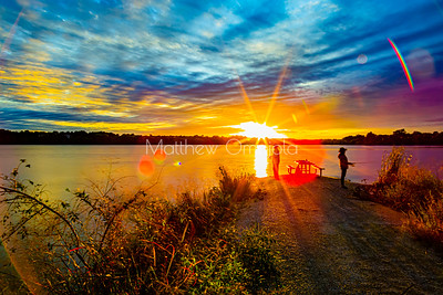 Intense golden hour sunset over Ed Zorinsky lake omaha. Dreamy sky colors. Sports fishermen silhouette with shadows.