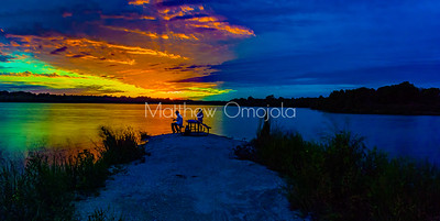 Panoramic Sunset colors reflecting on early fall autumn foliage. Foliage reflections in the lake. Sports fisherman silhouettes.  Dreamy sky colors with reflections on the lake..