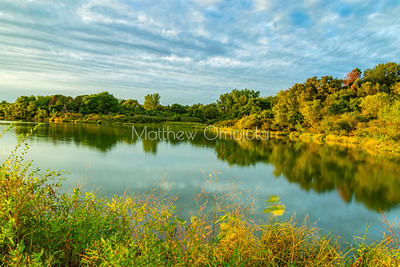 Early Fall foliage colors with reflection in Zorinsky lake at sunset. Beautiful foliage. Blue moving cloud.