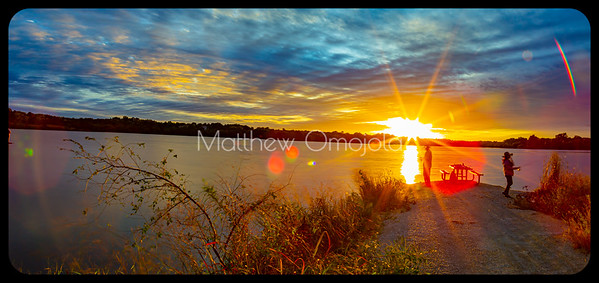 Panoramic golden hour sunset over Zorinsky lake Omaha Nebraska. Sports fishermen silhouettes and shadows. smudgy moving intense beautiful cloud colors
