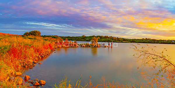 Dreamy sunset sky colors with moving clouds and early fall autumn foliage. Sports fishermen. Sky reflection in lake.