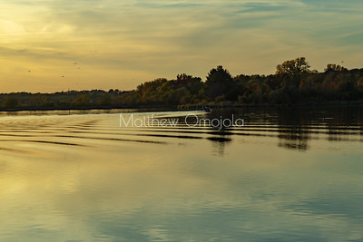 Fall autumn colors with sun and sky reflections in Ed Zorinsky Lake Omaha NE at sunset. Ripples in the lake .