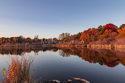 Fall autumn colors with reflections in Ed Zorinsky Lake Omaha NE at sunset.