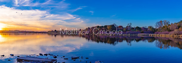 Panoramic view Fall autumn colors with forest, sun and sky reflections in Ed Zorinsky Lake Omaha NE at sunset.