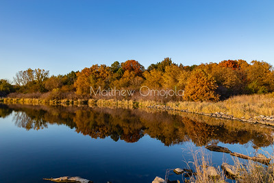 Fall colors with reflections in Ed Zorinsky Lake Omaha NE at sunset.