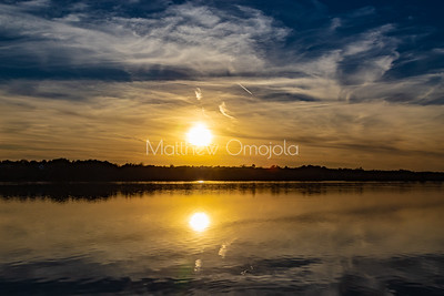Fall autumn colors with sun and sky reflections in Ed Zorinsky Lake Omaha NE at sunset.