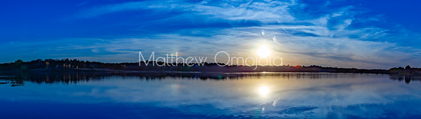 Panoramic view Fall autumn colors with sun and sky reflections in Ed Zorinsky Lake Omaha NE at sunset.
