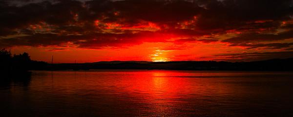 Red colored Cumulus cloud, sunset seascape.