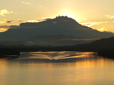 A boat going through the river while the sun rises over Mount Kinabalu, Sabah, Malaysia from Mengkabong Bridge.