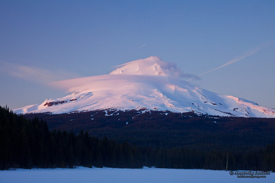 Mount Hood. View of snow capped Mt. Hood with frozen lake and forest in foreground, Oregon, U.S.A.